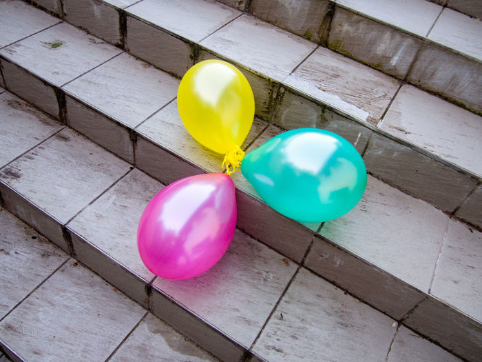 Accidental Beauty Balloon Balloons On The Ground Bright Celebration Close-up Colors Day Glossy Green Lines And Curves Missing Balloons Multi Colored No People Outdoors Party Pink Round Shape Shiny Stairs Still Life Three Tiles Tiles Textures Yellow