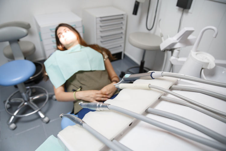 Close-Up Of Dental Equipment Against Female Patient Sitting In Clinic
