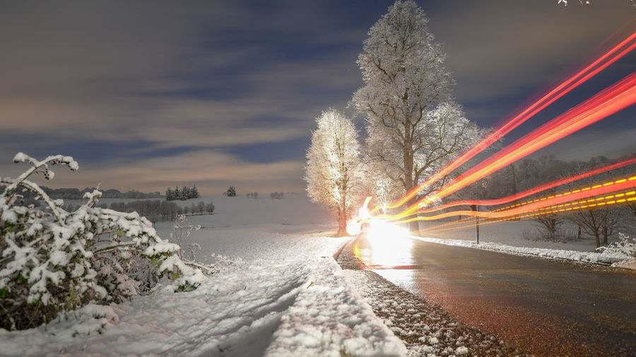 Light trails on road by trees against sky during sunset