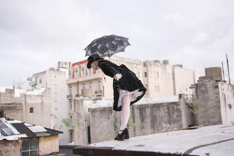 Full length of man flying bird against buildings in city
