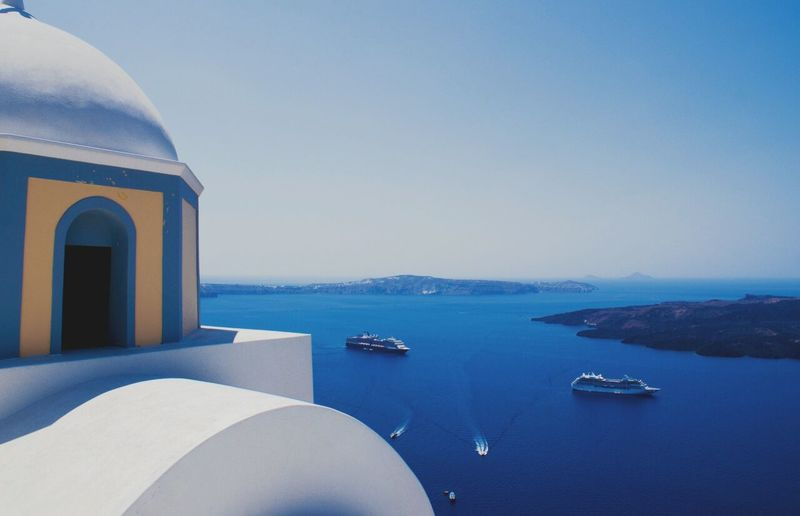 Cropped image of house by cruise ships sailing on sea against sky at santorini