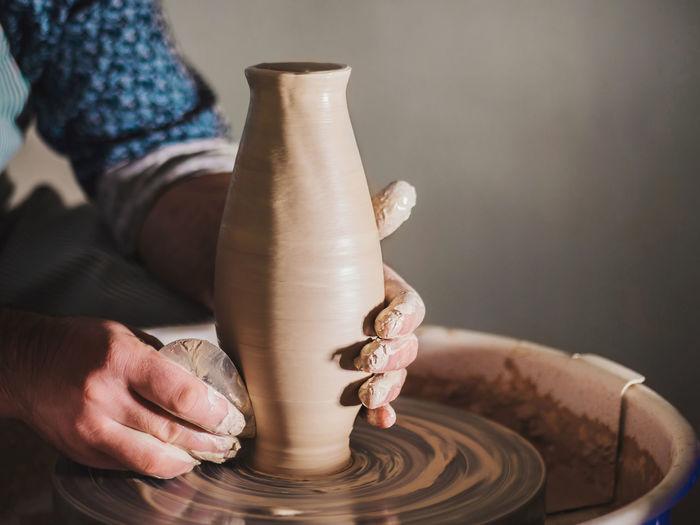 Cropped Hands Of Man Molding Pot In Workshop