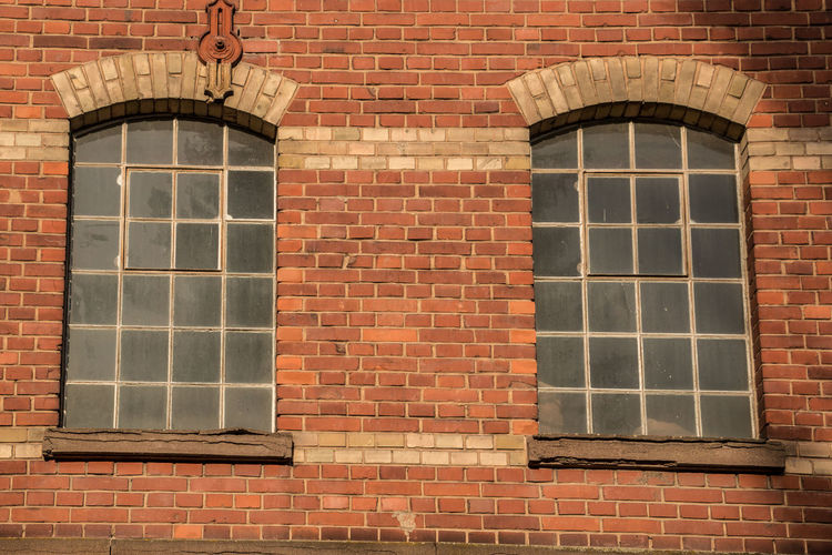 Old empty brick house factory with dark windows Brick Brick Wall Architecture Building Exterior Wall Built Structure Window Building Wall - Building Feature No People Day Red Pattern Outdoors City House Low Angle View Reflection Glass - Material Full Frame Window Frame