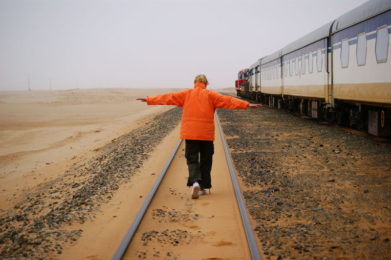 Rear View Of Woman With Arms Outstretched On Railroad Track Against Sky