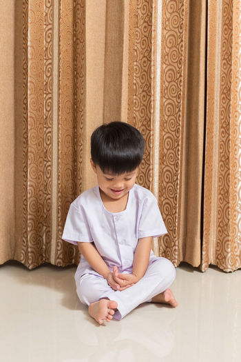 Boy Sitting Against Curtain At Home
