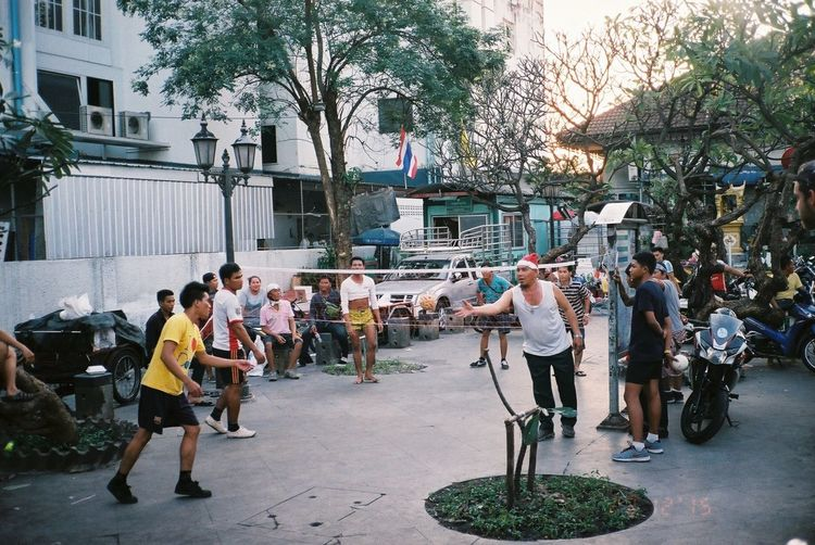 Men playing volleyball on street against buildings