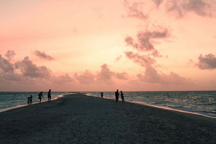 People on an atoll during sunset in the maldives
