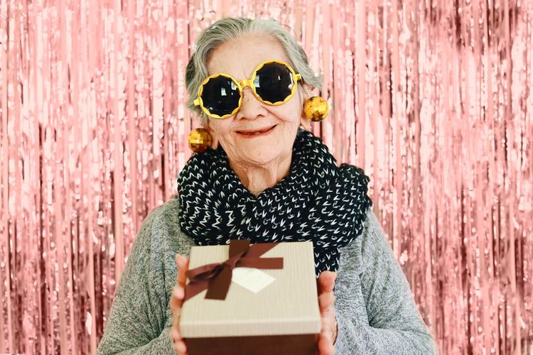 Portrait of smiling woman wearing sunglasses holding gift while standing against wall