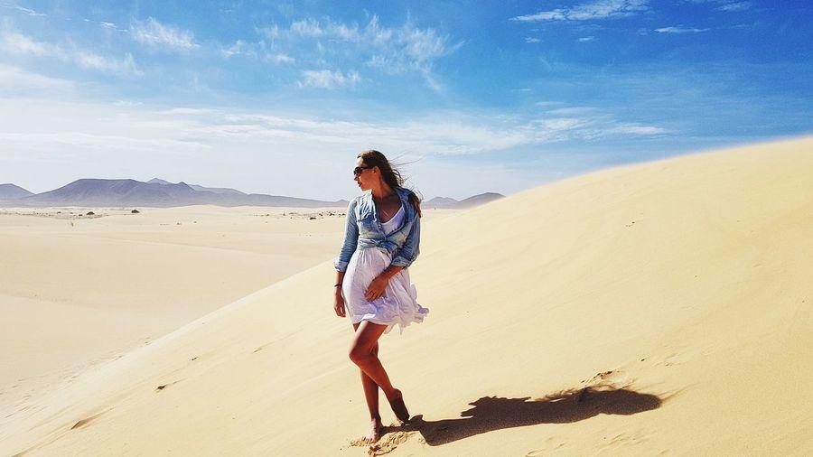 Full Length Of Woman On Sand Dune Against Sky