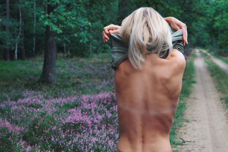 Rear view of woman removing clothes while standing in forest