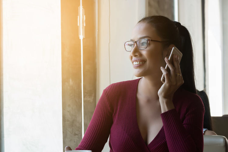 Smiling woman using mobile phone while looking through window