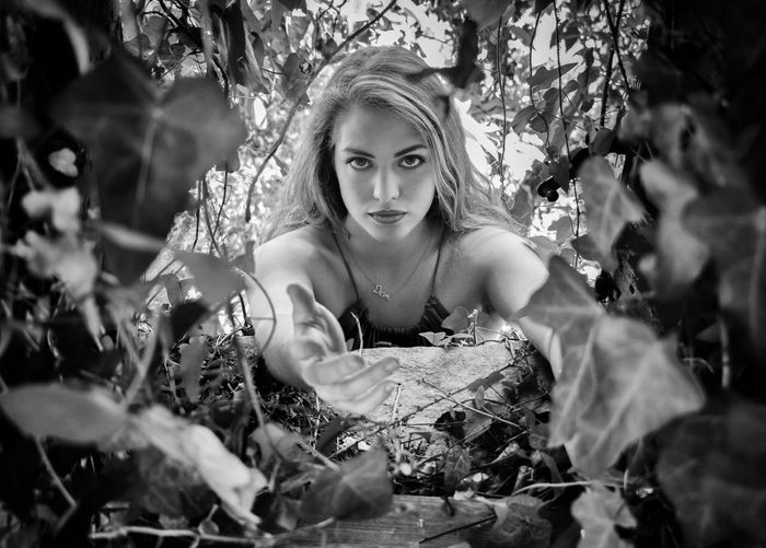 Portrait of young woman reaching amidst plants