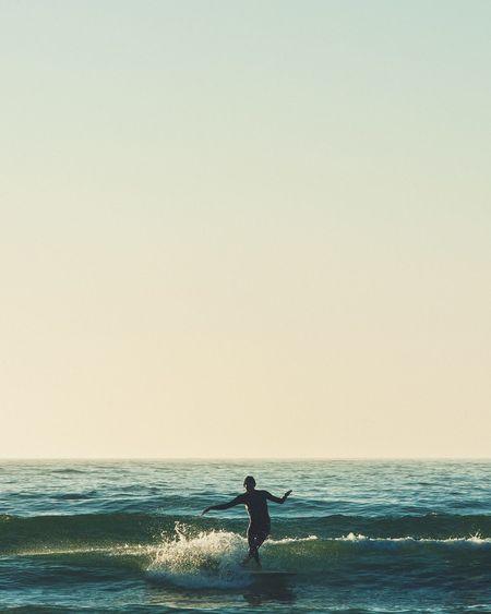 Silhouette man on beach against clear sky