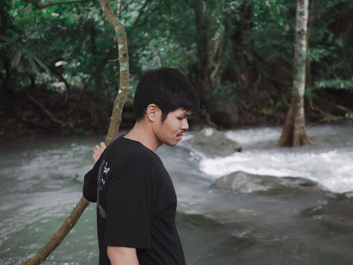 Adolescence  Casual Clothing Day Flowing Water Focus On Foreground Forest Land Leisure Activity Lifestyles Men Nature One Person Outdoors Real People River Standing Teenage Boys Teenager Tree Water Waterfall Young Adult Young Men