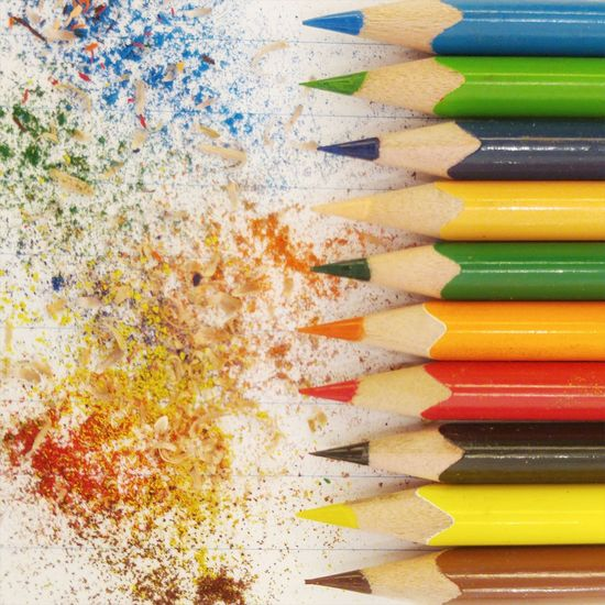 Row Of Colored Pencils By Shavings On Page