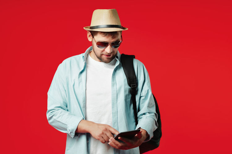 Young man wearing sunglasses standing against red background