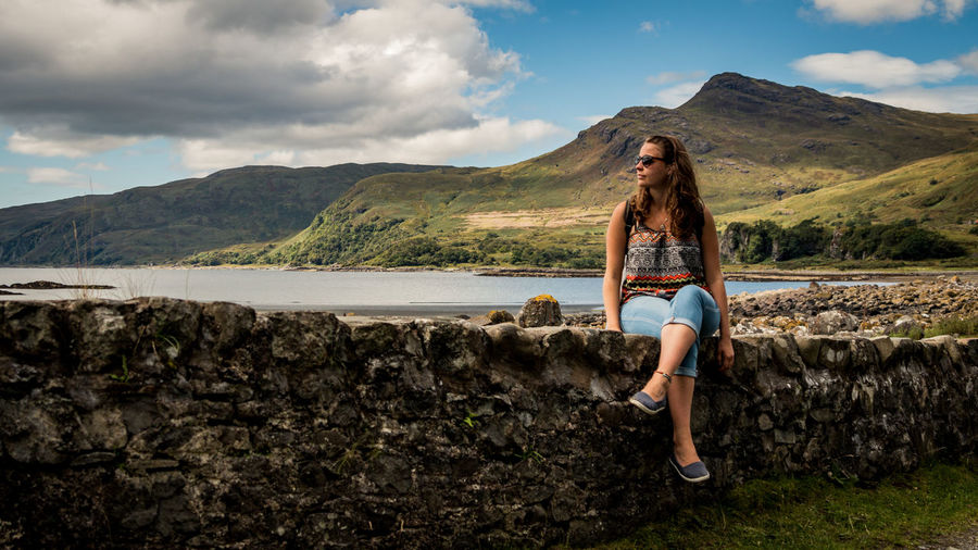 Young woman sitting on retaining wall at lakeshore against mountains
