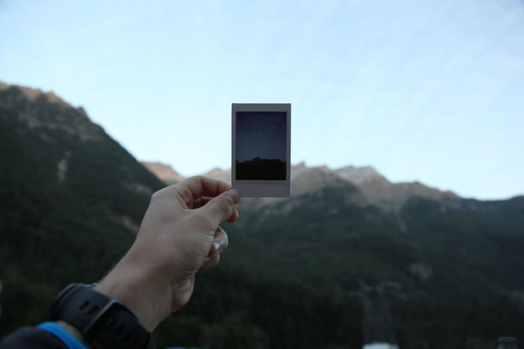Close-Up Of Hand Holding Instant Print Transfer Against Mountains