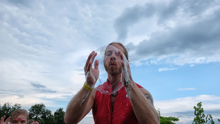 Bubble Artist Bubbles Arms Raised Cloud - Sky Day Emotion Eyes Closed  Front View Headshot Human Arm Human Body Part Lifestyles Low Angle View Magician Mouth Mouth Open Nature One Person Outdoors Portrait Real People Sky Waist Up