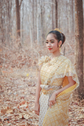 View of beautiful girl wearing traditional clothing standing in forest