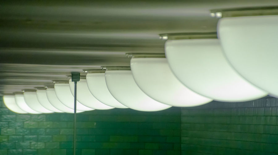 Row of illuminated recessed lights on ceiling