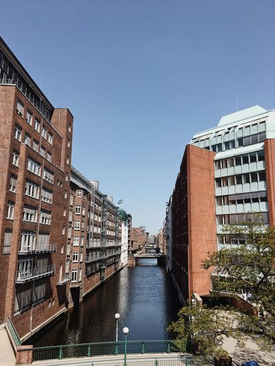 River amidst buildings against clear sky