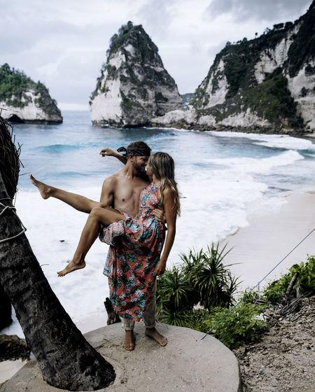 A couple at the famous diamond beach of nusa penida / bali.