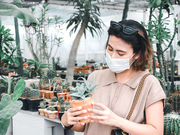 Close-up of woman holding potted plant in nursery