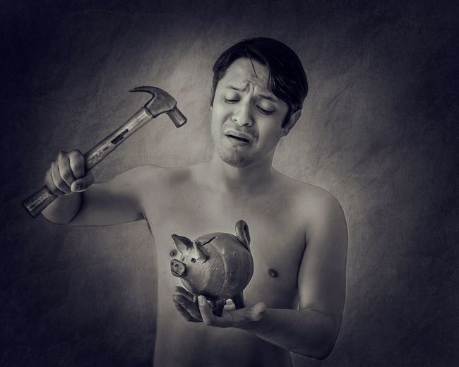 Shirtless mid adult man holding hammer and piggy bank while standing against wall