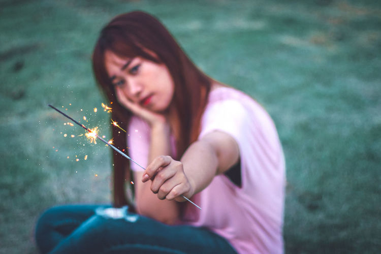 Portrait of woman holding sparkler while sitting on grass