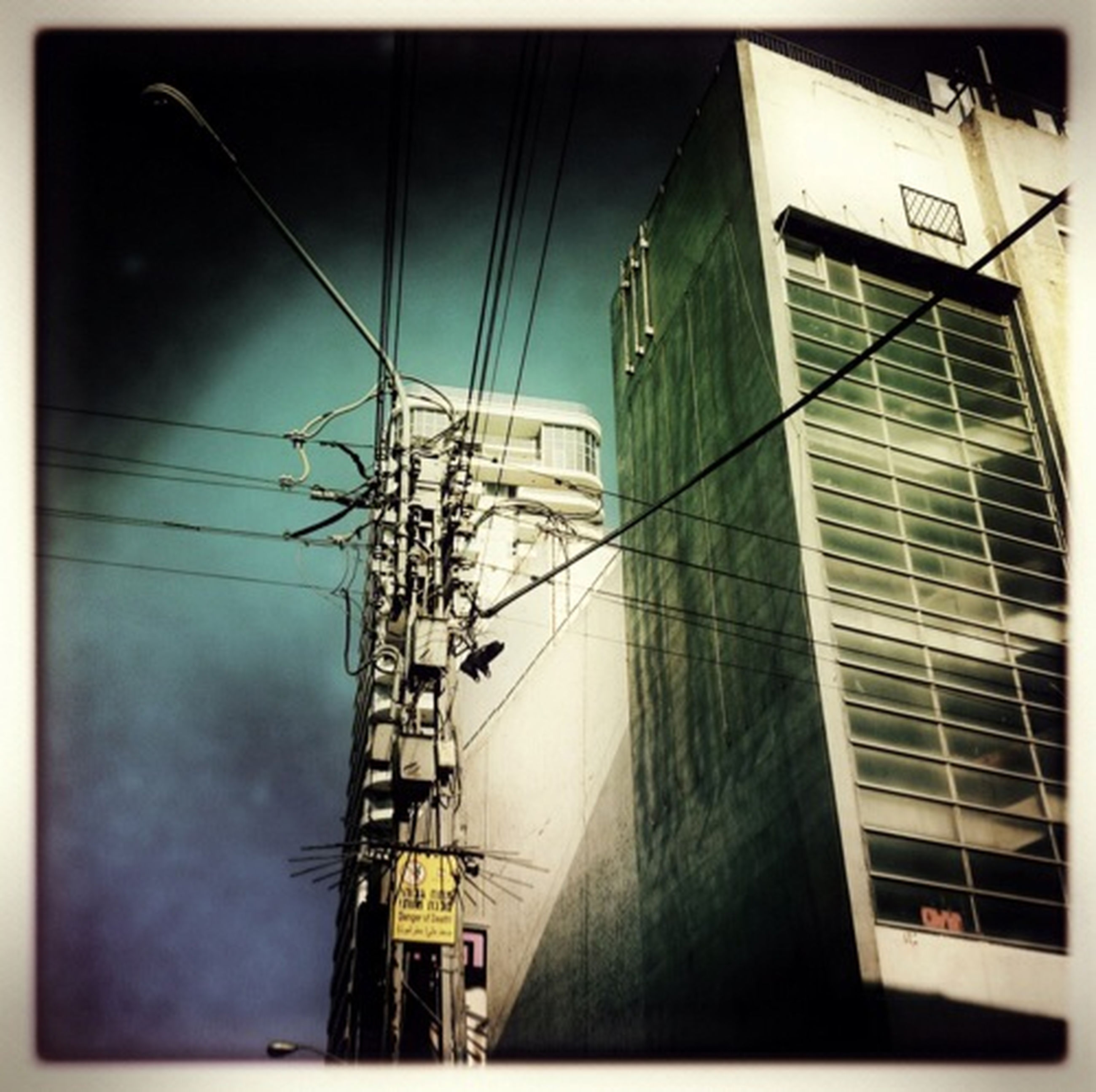 architecture, built structure, building exterior, power line, low angle view, transfer print, electricity pylon, electricity, cable, power supply, auto post production filter, connection, sky, building, fuel and power generation, city, technology, day, outdoors, no people