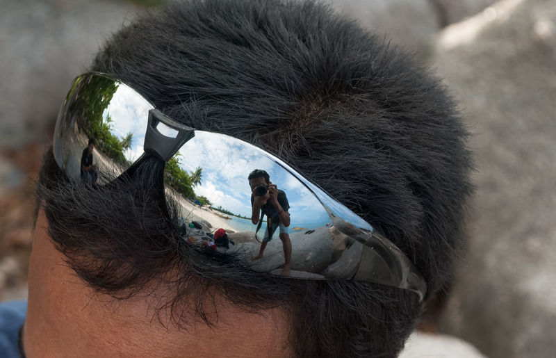 Man Photographing With Camera Reflecting On Sunglasses Of Man At Beach