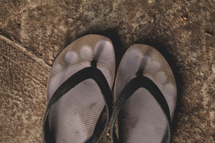 Close-up of flip-flops on floor