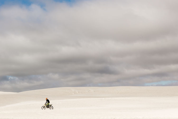 Man riding motorcycle on sand against cloudy sky