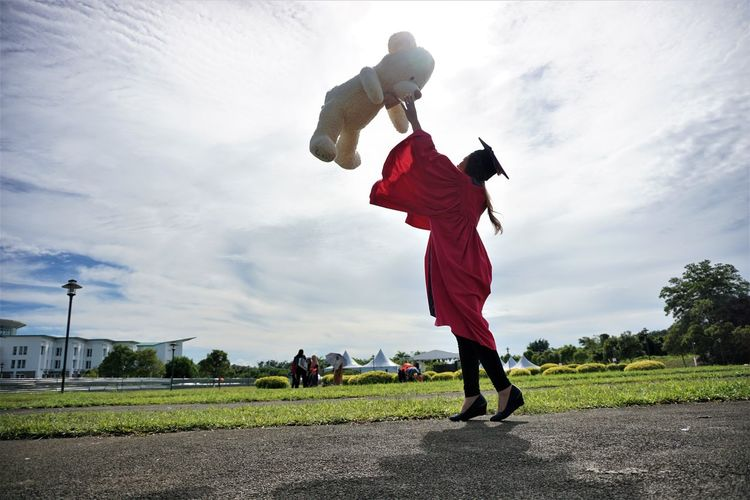 University student throwing teddy bear against sky during graduation