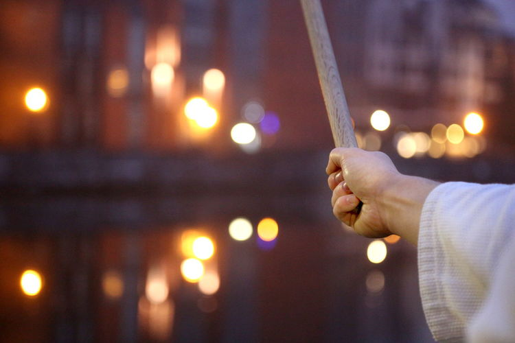 Cropped image of man practicing martial arts with sword against illuminated canal in city during sunset