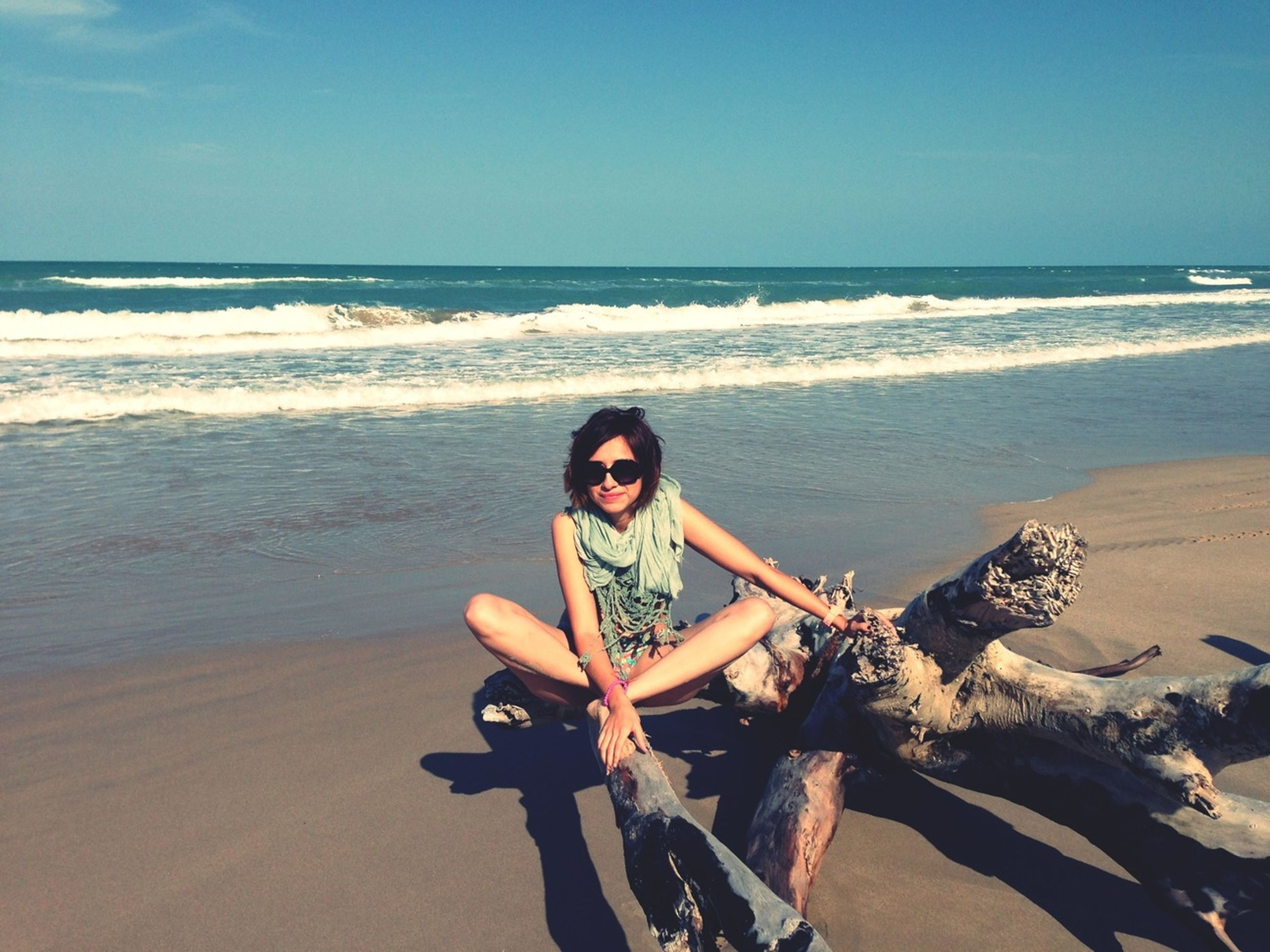 sea, beach, horizon over water, young adult, water, lifestyles, leisure activity, shore, person, young women, sand, clear sky, vacations, looking at camera, sunglasses, portrait, casual clothing, sitting