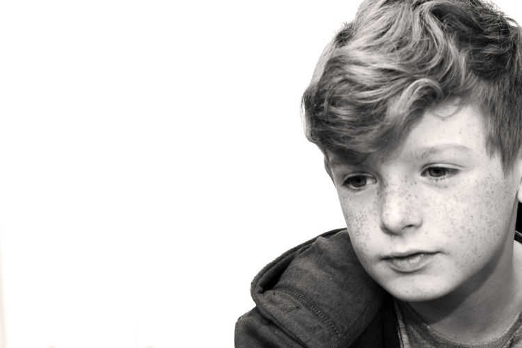 Black and white photo of a boy looking away from the camera. Adolescence  Boys Child Childhood Close-up Contemplation Copy Space Front View Headshot Human Face Indoors  Lifestyles Looking At Camera Males  Men One Person Portrait Pre-adolescent Child Studio Shot Teenager White Background