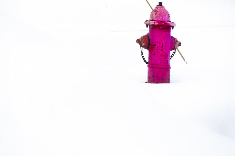 Close-up of fire hydrant on snow against white background