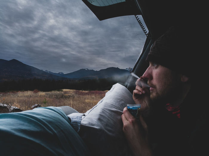 Close-Up Of Man Smoking Cigarette In Tent Against Cloudy Sky