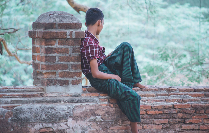 Side view of teenage girl sitting on stone wall