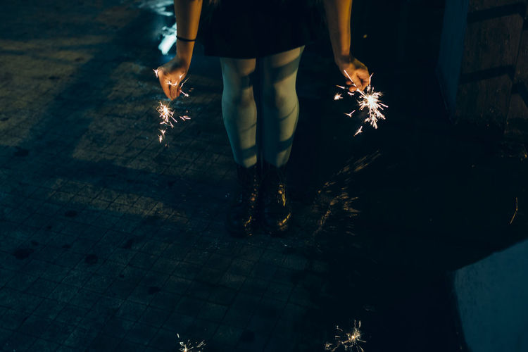 Low section of woman holding sparklers while standing on footpath at night