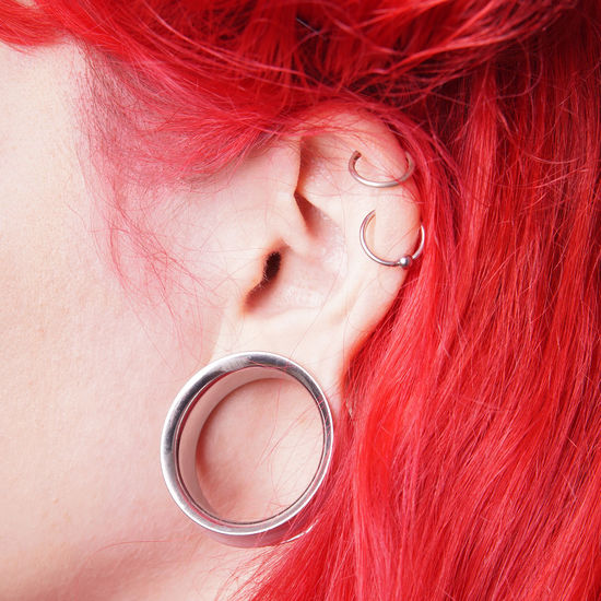 Cropped image of woman with redhead wearing earring