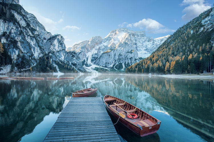 Boats Moored At Lake By Snowcapped Mountains Against Sky