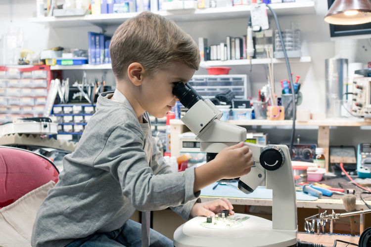 Boy using microscope while sitting on table