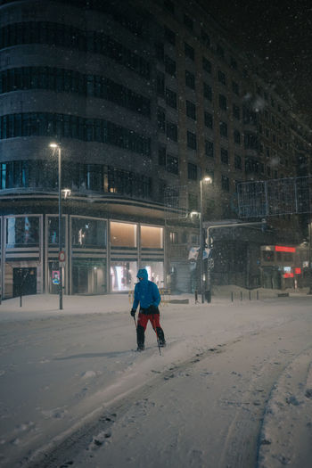 Rear view of man on snow covered street at night