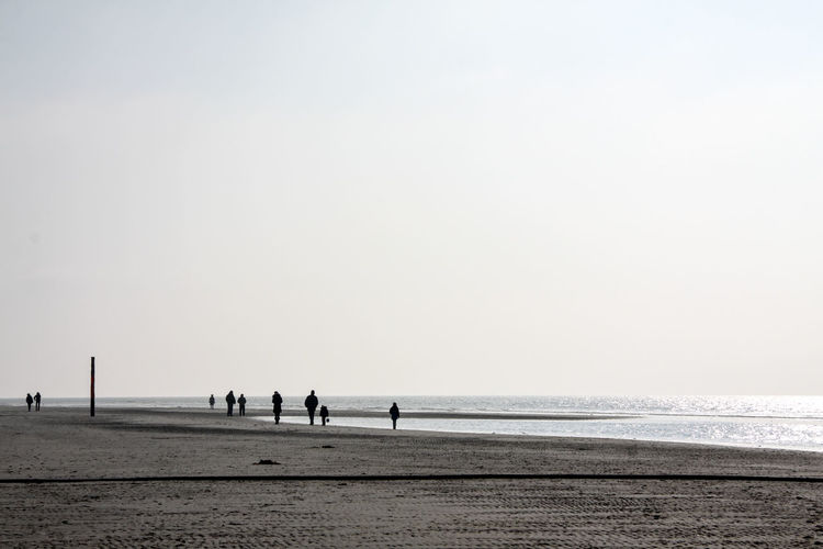 Silhouette People On Beach Against Clear Sky