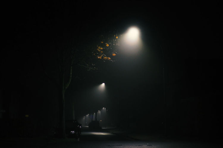 Illuminated street light on road at night