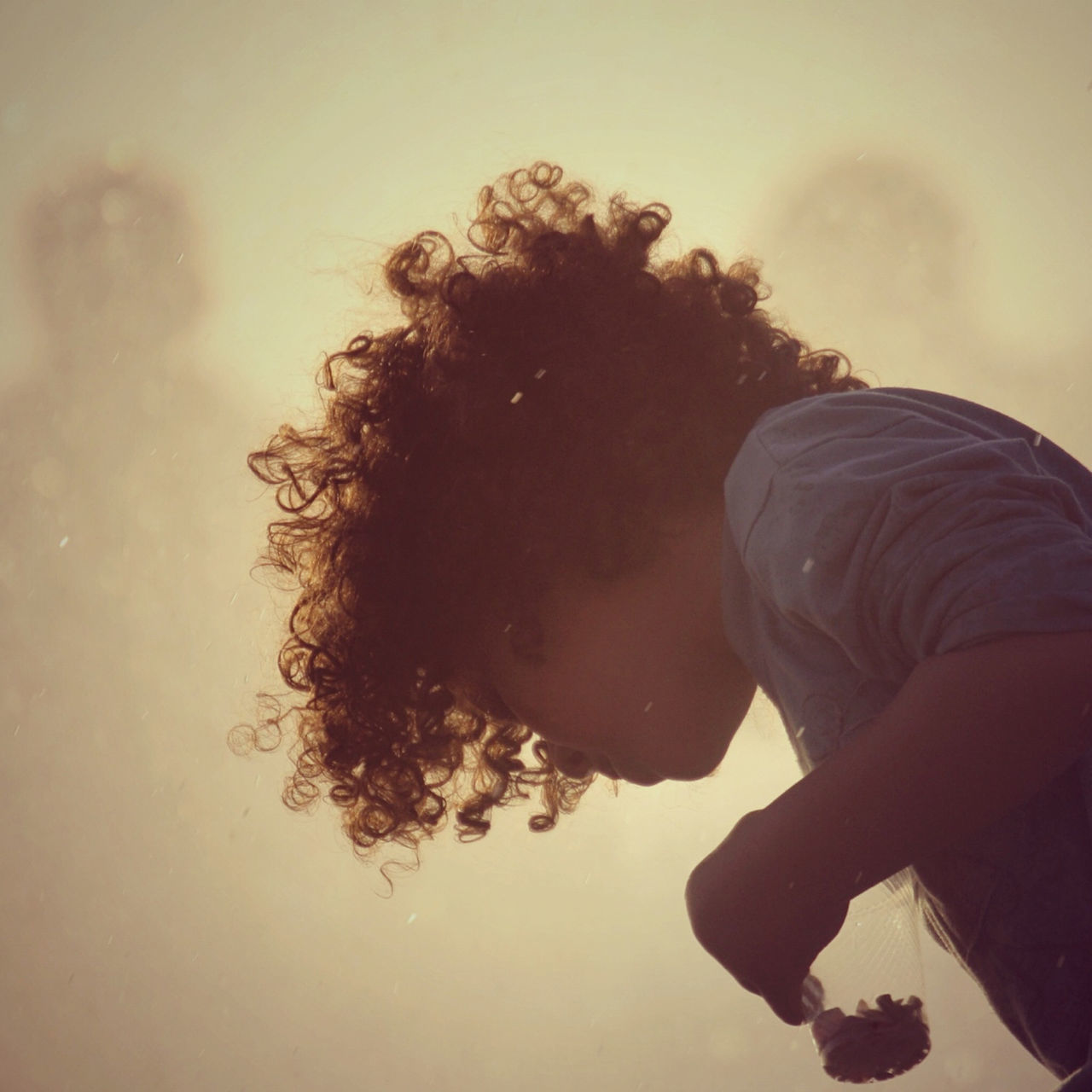 Boy with curly hair standing outdoors
