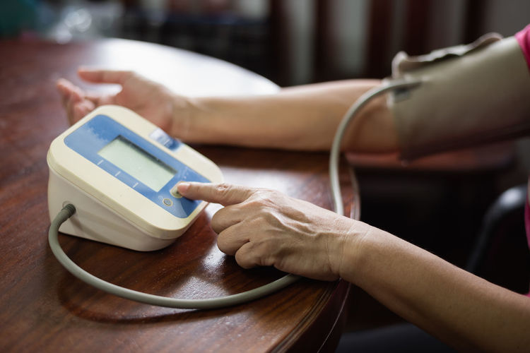 Cropped hands of woman using blood pressure gauge at table